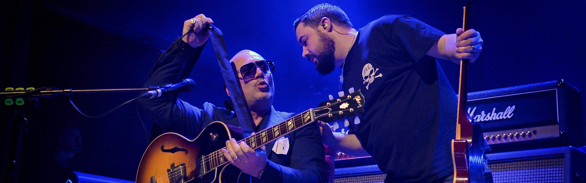 Brendon Riley of Shire Guitars provides technical assistance to Huey of Fun Lovin' Criminals. Pic courtesy of Perry Smylie Photography