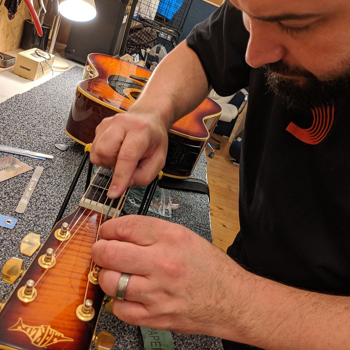 Brendon Riley of Shire Guitars servicing a Marlin electro-acoustic guitar